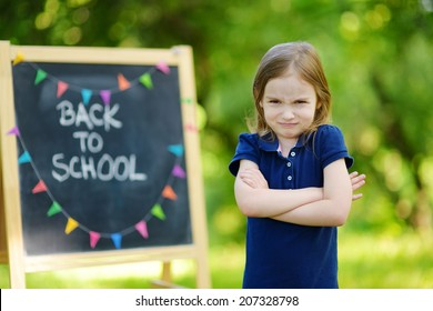 Adorable little schoolgirl feeling unhappy about going back to school