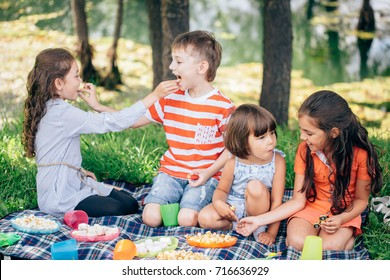adorable little sibling kids eating in park outdoors. Feeding each other.