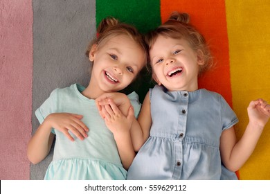 Adorable little sisters lying on colourful carpet, top view