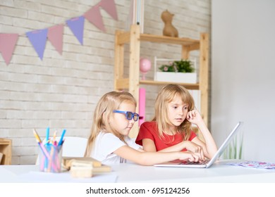 Adorable little sisters playing educational game on laptop while enjoying summer day at home, interior of cozy bedroom on background