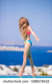 Adorable little slim girl on the edge of outdoor swimming pool with beautiful view