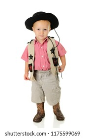 An adorable little, standing cowboy, looking shyly at the viewer. On a white background.