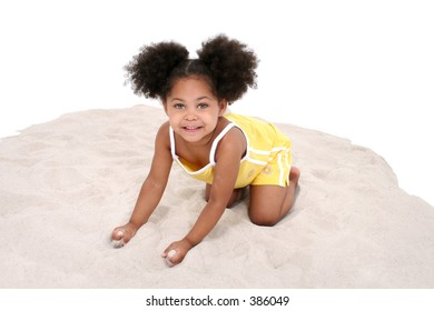 Adorable little three year old girl in yellow playing in the sand.  Shot in studio over white (and sand)