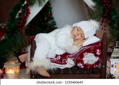 Adorable little toddler baby boy dressed in canta claus costume, sleeping in baby bed in front of teepee decorated for Christmas