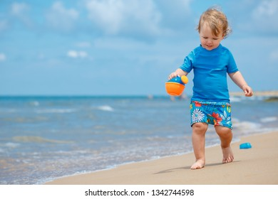 Adorable little toddler girl playing on sand beach during summer holiday vacation