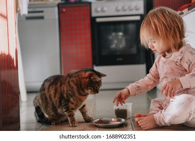 Adorable little toddler girl in sleepwear feeding domestic cat dry food in the kitchen