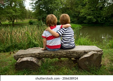 Adorable Little Twin Brothers Sitting on a Wooden Bench, Embracing Each Other and Looking at Beautiful Lake at Summer