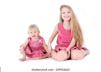 adorable little two sisters 9 year and  1  year old on white background