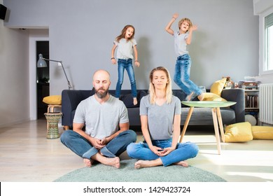 Adorable and lively siblings playing on sofa while parents sitting in lotus pose and meditate
