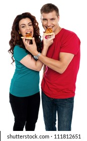 Adorable love couple enjoying pizza pie together. Both making each other enjoy pizza piece