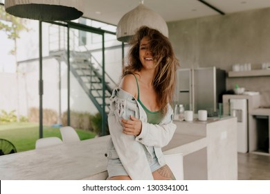 Adorable lovely lady with curls qearing denim jacket and shorts has fun outside in summer good day, her hair flying at camer, background modern house