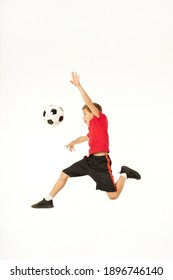 Adorable male child jumping and playing football