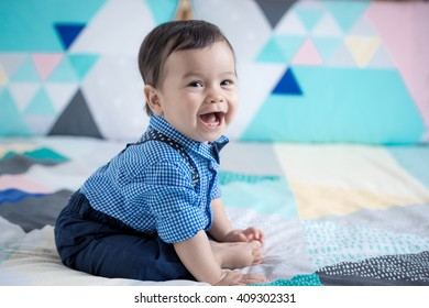 Adorable mixed race 11 month old Asian Caucasian boy plays cheerfully on a colorful geometrically shaped bed cover. Natural indoor lighting.