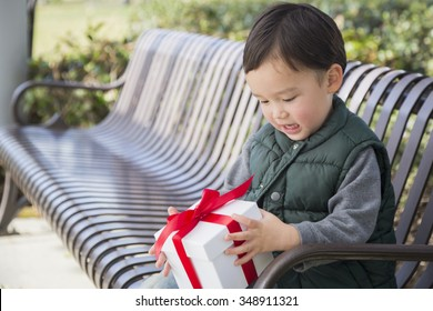 Adorable Mixed Race Boy Opening A Christmas Gift Outdoors On A Bench.
