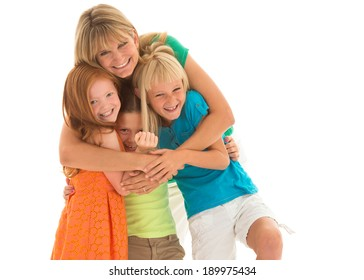 Adorable mom hugs vibrantly dressed daughters. Studio shot, isolated on white background.