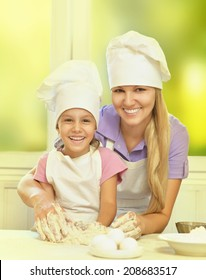 Adorable mother and daughter cooking together in the kitchen