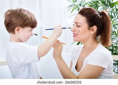 Adorable mother and son playing with watercolors and brushes