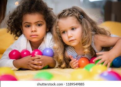 adorable multicultural kids lying with colorful balls in kindergarten
