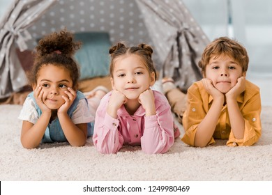 adorable multiethnic children lying on carpet and looking at camera