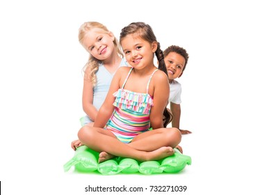 335c77ddb52fe adorable multiethnic kids in swimwear sitting on swimming mattress and  smiling at camera