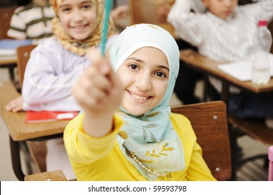 Adorable Muslim girl in classroom with her friends children students