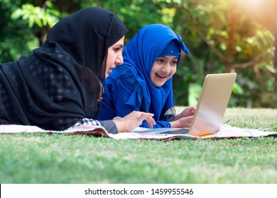 Adorable muslim little girl and mom enjoying outdoors using laptop, Asian muslim little girl and mom playing on laptop at park in summer
