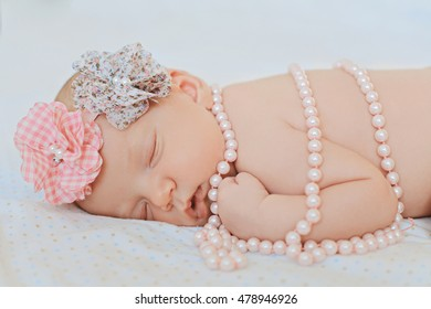 Adorable new born child peacefully sleeping on white blanket wearing a large, fabric rose headband and bead. Nursery for newborn baby. Family Bedding. Healthy little infant girl shortly after birth.
