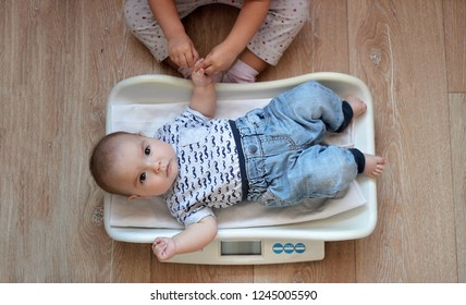 Adorable newborn baby boy lying on the baby weight scale at home, his sister holding his with hand, healthy growth and family care