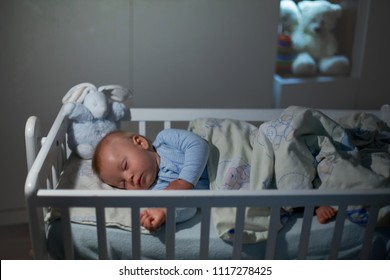 Adorable newborn baby boy, sleeping in crib at night. Little boy in white pajamas taking a nap in dark room. Bedroom interior with lamp and teddy bear in the background