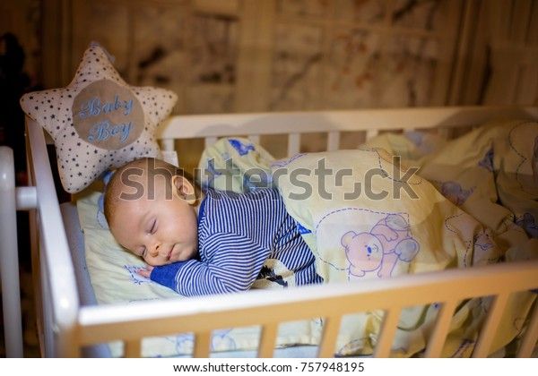 Adorable newborn baby boy, sleeping in crib at night. Little boy in blue striped pajamas taking a nap in dark room, christmas decoration in the room, winter time, snowing outdoors