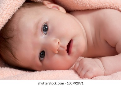 Adorable newborn baby girl is looking at the camera