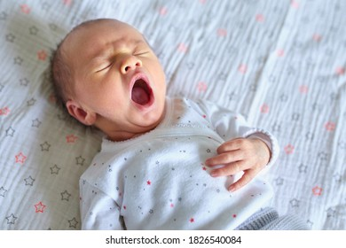 Adorable newborn baby girl sleeping and yawning in bed at home