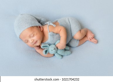 Adorable newborn baby lies on grey blanket