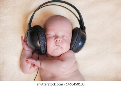 adorable newborn baby sleeping with large black earphones