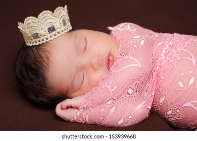 Adorable newborn baby sleeping wrapped on pink lace on brown cushion with a crown on the head.