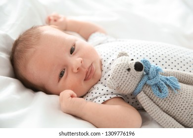 Adorable newborn baby with toy lying on bed sheet