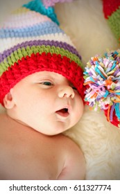 Adorable newborn boy with funny striped knitted hat