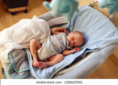 Adorable newborn boy sleeping in bouncer chair and dreaming