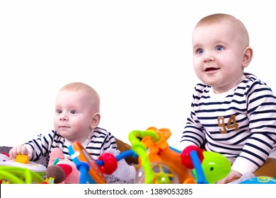 Adorable non-identical twins, also known as fraternal twins or dizygotic twins play with toys isolated on white background. Two happy boys, one sitting and one lying. Pretty toddlers.
