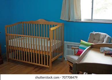 Adorable nursery with hardwood floors, a wooden crib and changing table, brown rocking chair with a rainbow pillow, and window with simple curtains above a white cast iron radiator
