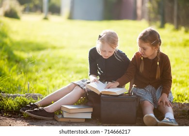 Adorable old-fashioned happy little 6 years old and 10 years old girls reading and smiling, back to school chalkboard. Preschooler and schoolgirl sisters, schoolkids.