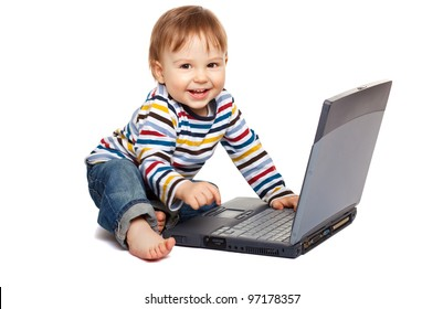 Adorable one year old child using laptop and having a great fun, isolated on white