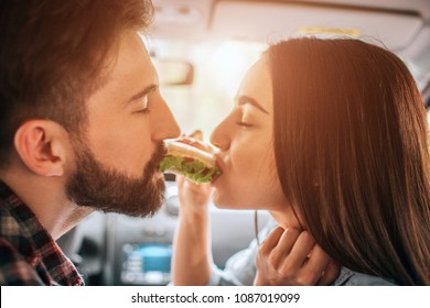 Adorable people are sitting in car and eating one sandwich from both sides of it. They are keeping their eyes closed and enjoying the moment. Close up.