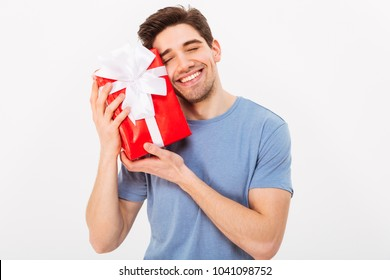 Adorable photo of attractive man with beautiful smile leaning his head to birthday present box isolated over white wall