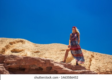 adorable photogenic model portrait in  domineering pose foreshortening from below with long Eastern entourage colorful dress stay on top of desert canyon rock on blue sky background, copy space