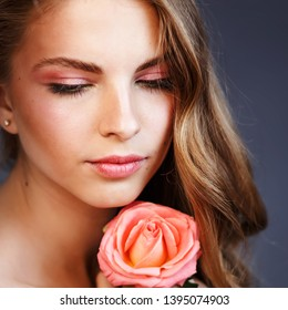 Adorable pink lips of young woman with rose in hand.