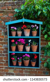 Adorable planter box hanging on a brick wall with brightly colored potted plants.