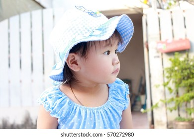 An adorable portrait asian little baby girl 1 year 8 months wearing blue cloth and bucket hat.Blue patterns