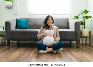 Adorable pregnant woman in her 30s sitting on her living room floor and showing her pretty belly. Attractive expectant mother smiling and posing at home
