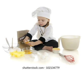 "An adorable preschool ""chef"" cracking eggs as she makes her first cake.  On a white background."